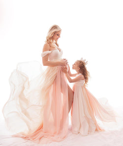 Pregnant mother in the Julia Gown by Sew Trendy Accessories in Peachy Natural Ombre in a studio.