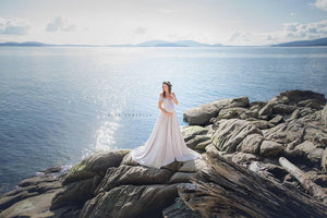 Pregnant mother in the Kinsey Gown by Sew Trendy Accessories in Grey standing on a rock near water.