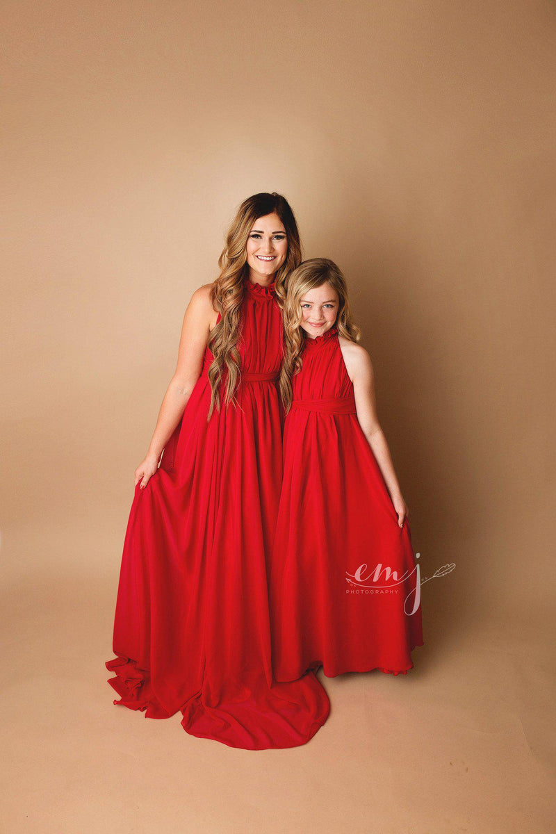 Pregnant woman wearing the Carolynne gown in red by Sew Trendy standing next to daughter in studio