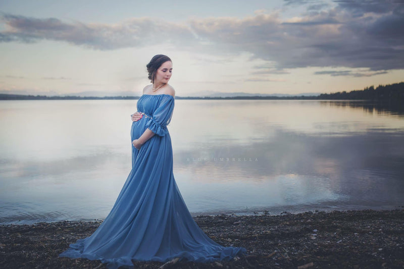 Pregnant Woman in the Paulina Gown in Blue Steel by Sew Trendy Accessories standing at a lake with water in the background.