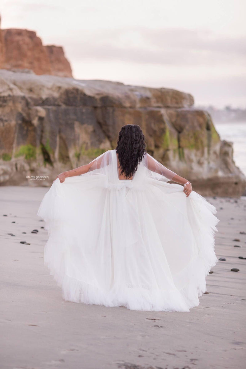 Pregnant woman wearing Winefred in white by Sew Trendy standing on beach by ocean