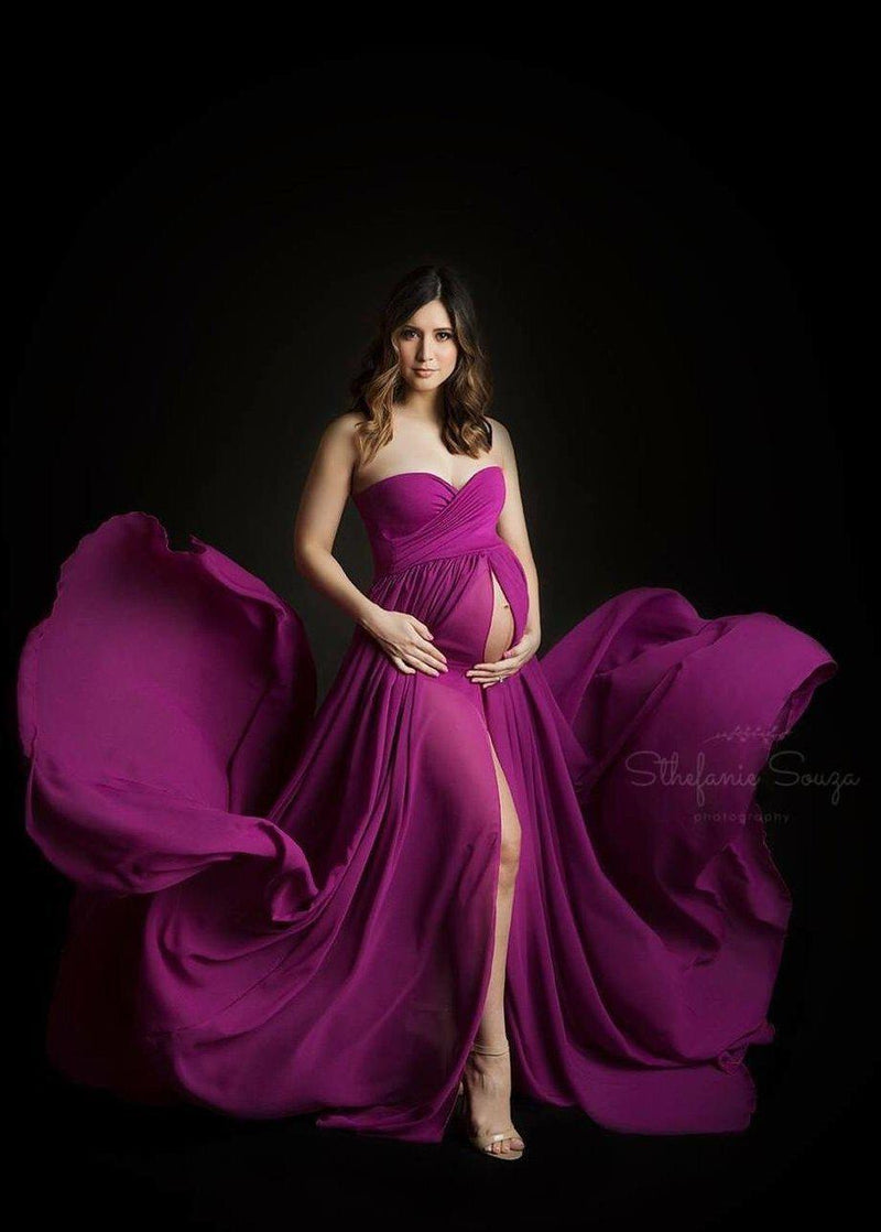 Pregnant woman in the Raquel Gown in Magenta by Sew Trendy Accessories standing in a studio on a black backdrop.