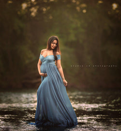 Expecting mother wearing the Faythe gown in steel blue by Sew Trendy standing in river at sunset