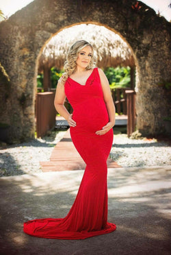 Pregnant woman in the Rue Gown in Red by Sew Trendy Accessories standing in front of a stone archway.