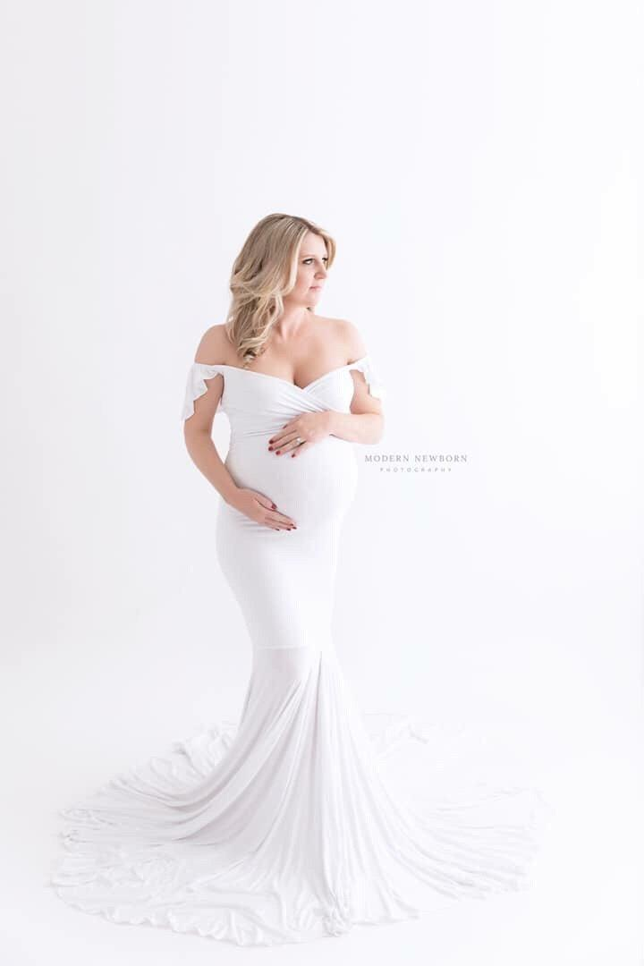 Expecting mother wearing the Serenity in white by Sew Trendy standing in studio on white backdrop