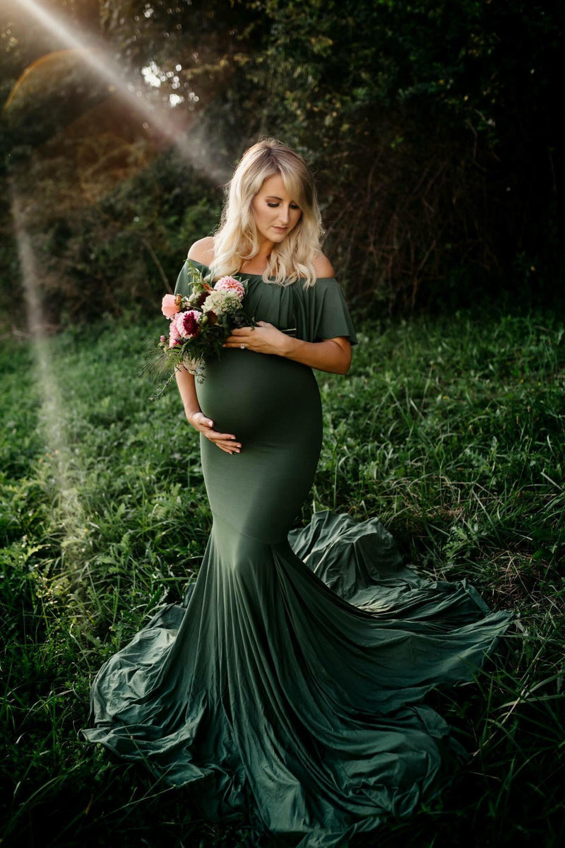 Pregnant woman wearing the Cirenya gown in evergreen by Sew Trendy, standing in field holding flowers.
