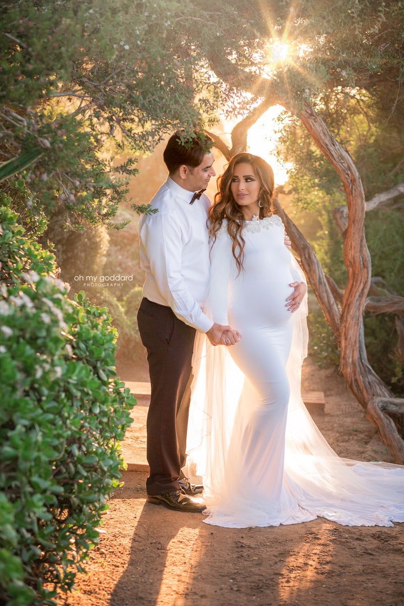 Beautiful pregnant woman wearing the Ravenna bridal mesh cape over her Sew Trendy gown in White standing with her husband at sunset