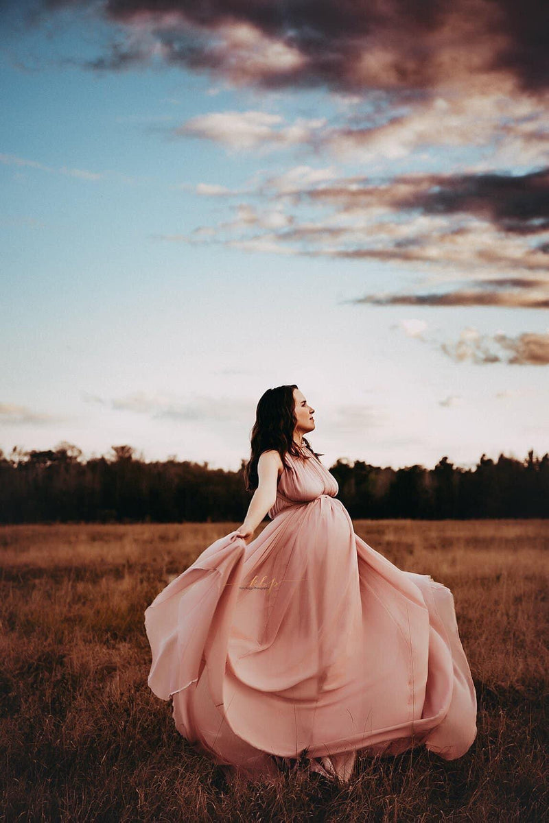 Pregnant woman wearing the Carolynne gown in mauve by Sew Trendy standing in field at dusk