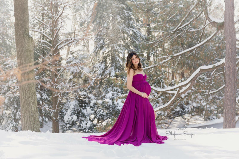 Pregnant woman in the Raquel Gown in Magenta by Sew Trendy Accessories standing in the snow with trees.