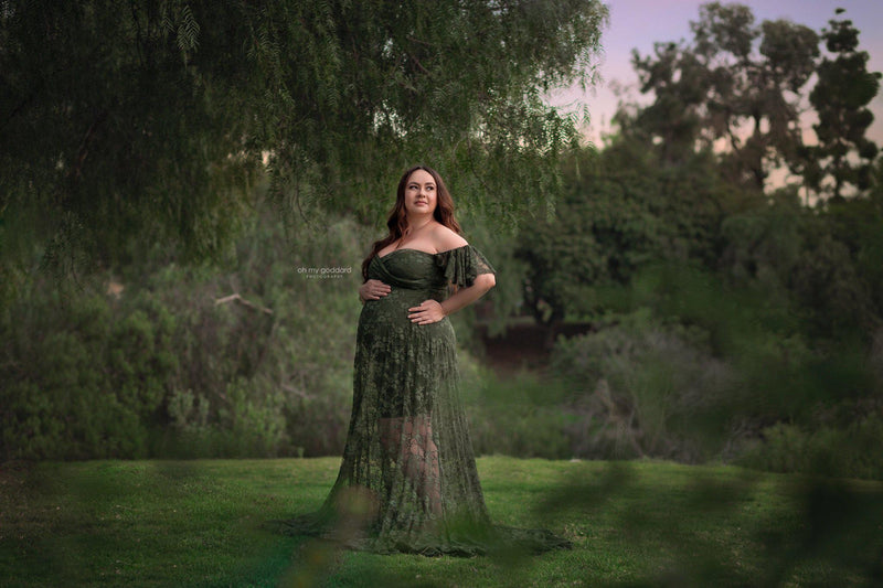 Pregnant woman in the Persephone Gown in Evergreen by Sew Trendy Accessories surrounded by green trees.