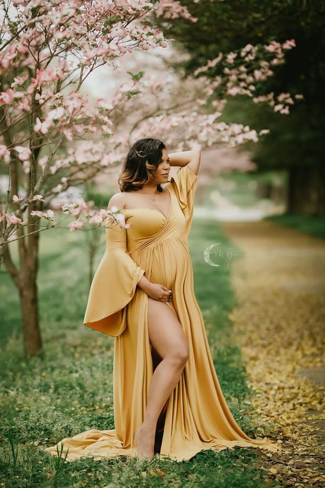 Expecting mother wearing Wren gown in gold by Sew Trendy standing in cherry blossoms