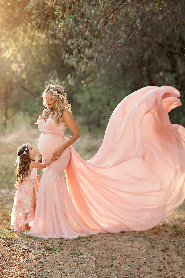 Beautiful pregnant mother wearing the annalise gown and butterfly tossing train standing with her daughter on a forrest path