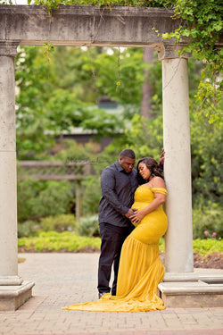 Expecting mother wearing the Amorah gown in gold by Sew Trendy with her husband standing in a garden.