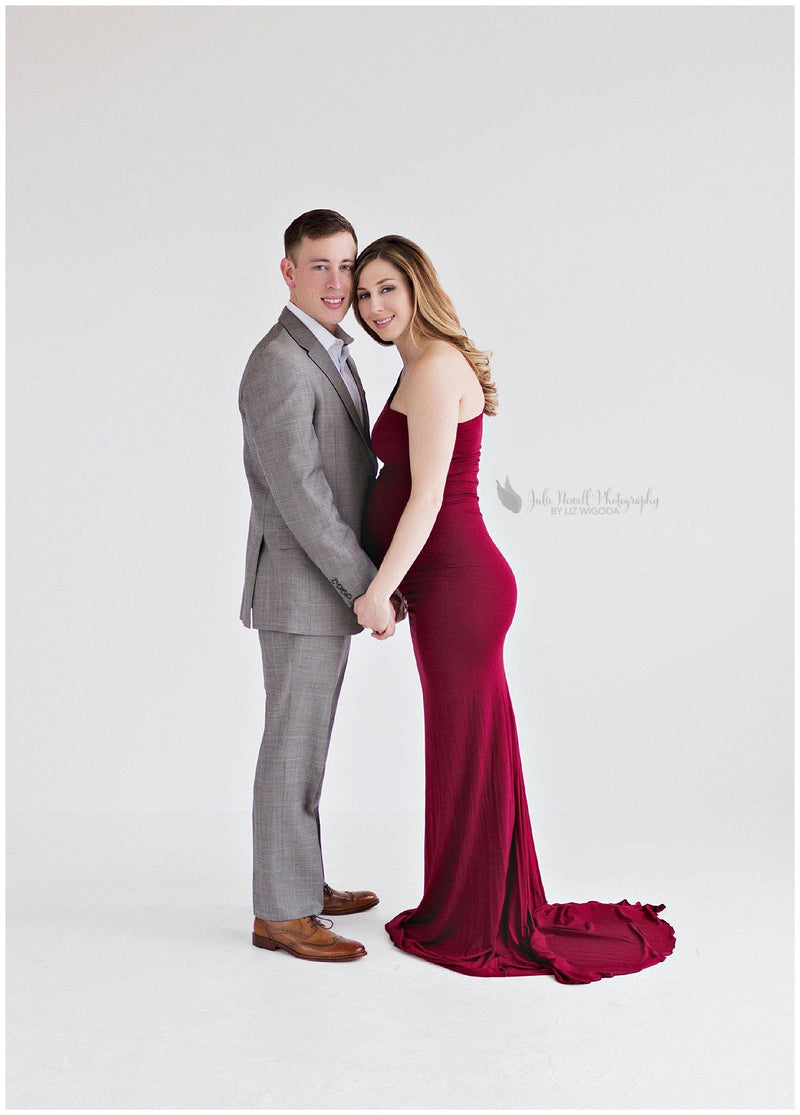 Pregnant mother wearing the Anita gown in wine by Sew Trendy standing with husband in studio.