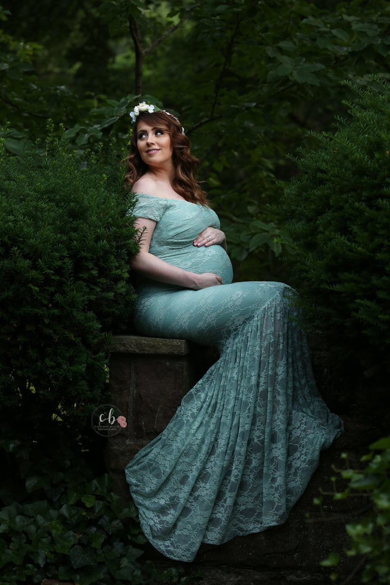 Pregnant woman wearing the bella gown in sage by Sew Trendy sitting in forrest.