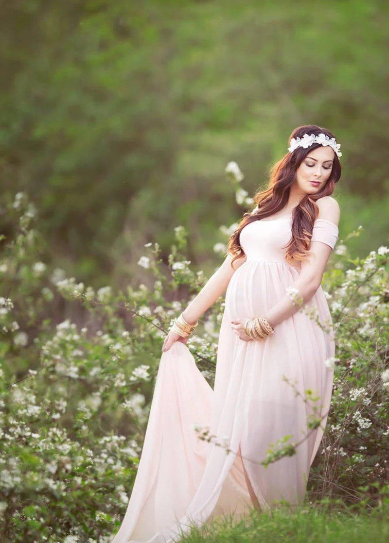 Expecting mother wearing the Cameron gown in blush by Sew Trendy standing in spring blossoms