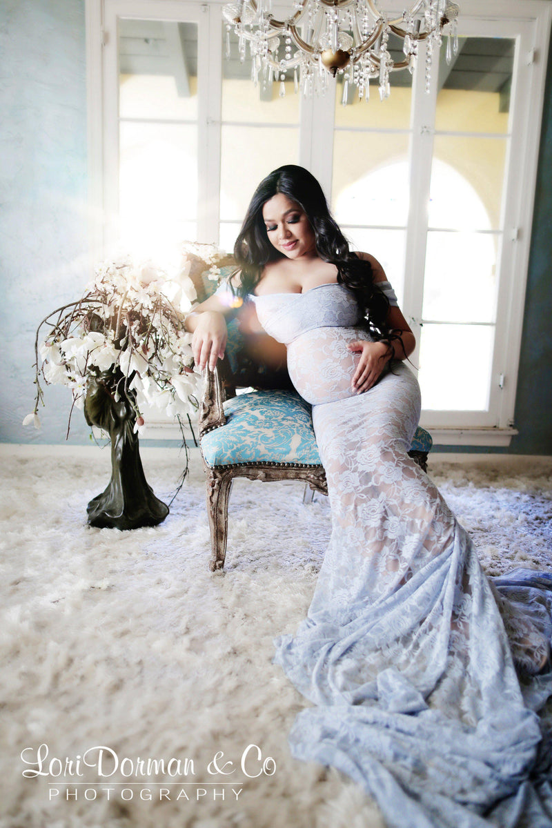 Expecting mother wearing the Catherine gown in blue rain by Sew Trendy sitting on victorian chair in studio