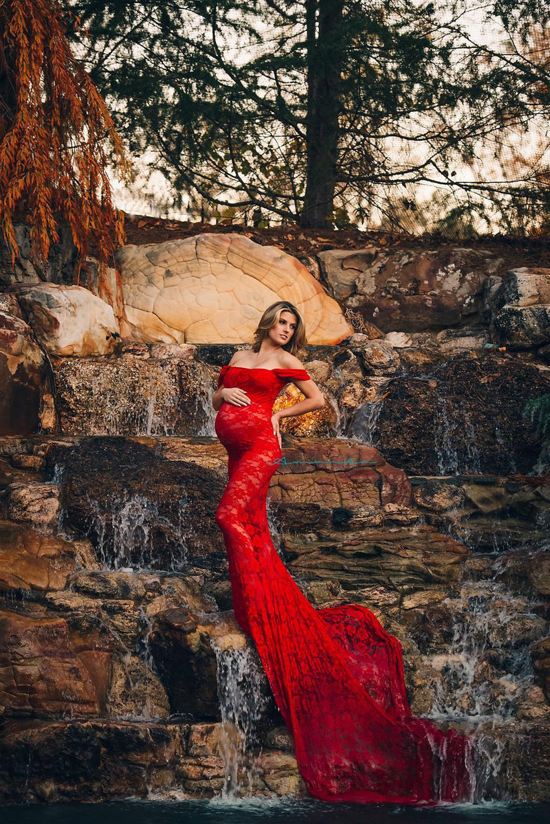 Expecting mother wearing the Catherine gown in red by Sew Trendy standing on cliff face