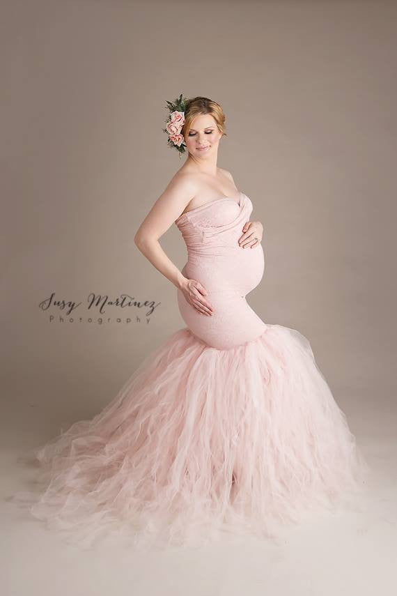 Pregnant woman wearing Celine gown in blush by Sew Trendy standing in studio on taupe backdrop