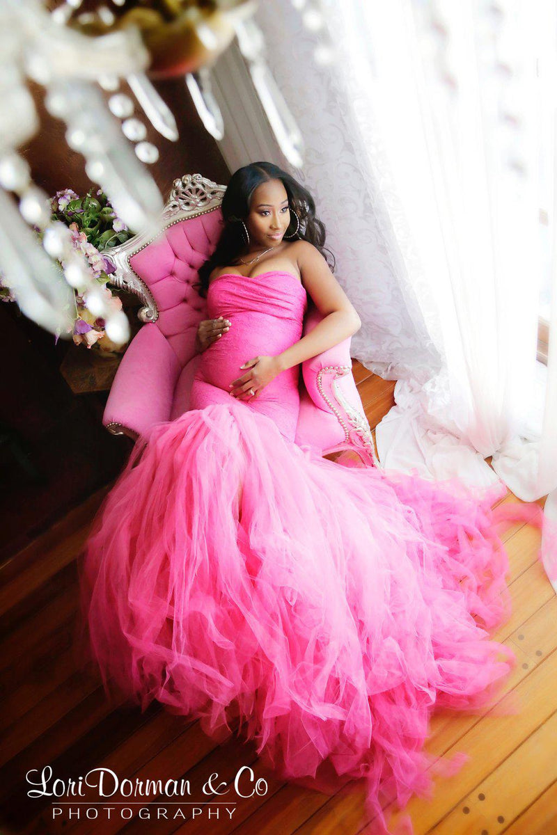 Pregnant woman wearing Celine gown in fuchsia by Sew Trendy sitting in pink chair by window with chandelier above