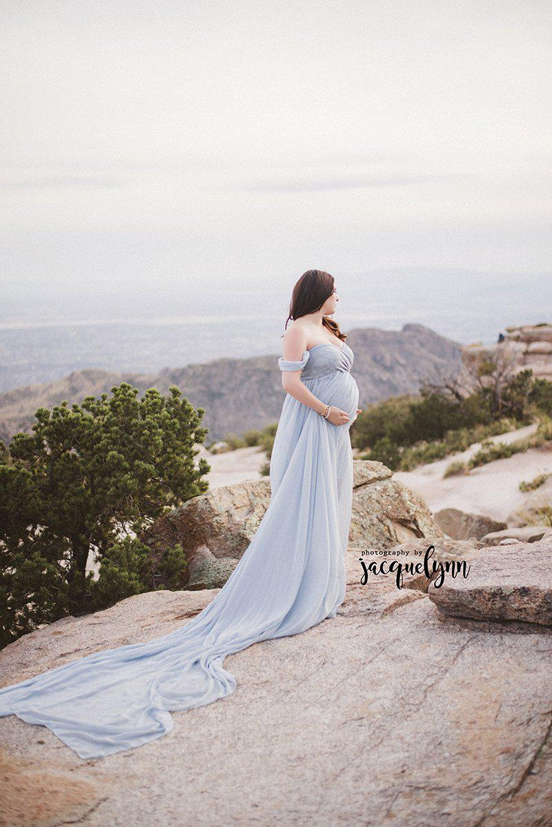 Expecting mother wearing the Eira gown in blue rain by Sew Trendy standing on cliff over valley