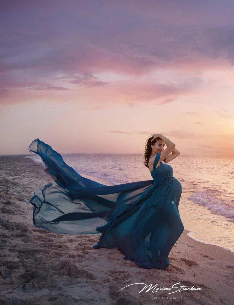 Expecting mother wearing the Eira gown in teal by Sew Trendy standing beach at sunset