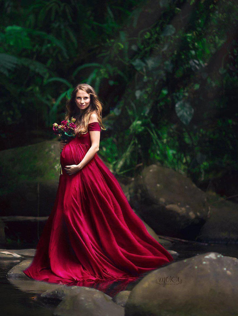 Expecting mother wearing the Faythe gown in wine by Sew Trendy standing near river with flower bouquet