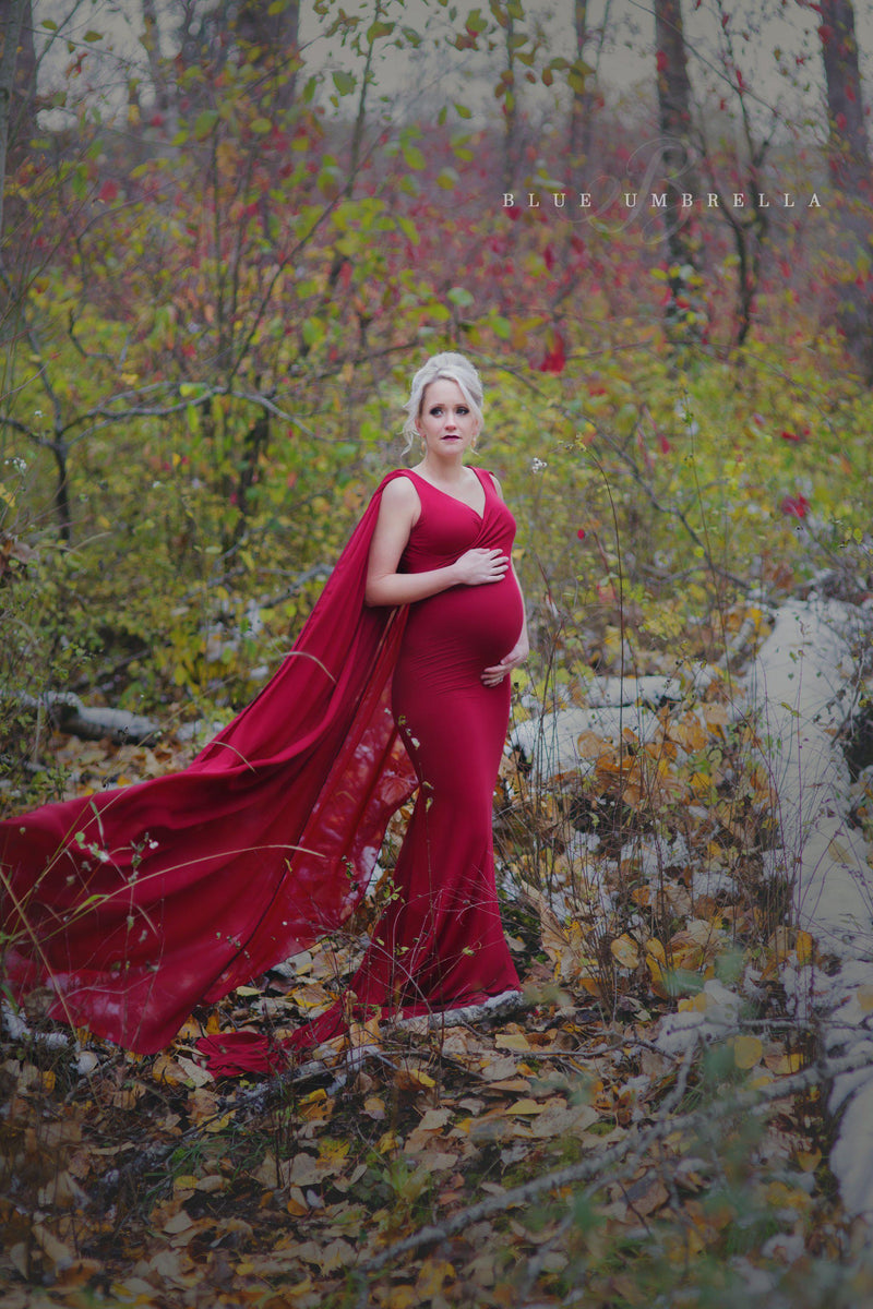 Expecting mother wearing the Hera gown in red in a forest by Sew Trendy Accessories
