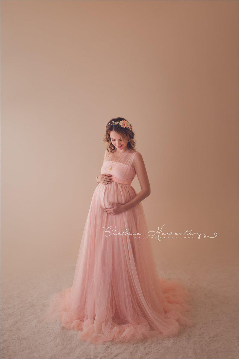 Kaitlyn Gown-Maternity Gown-Sew Pregnant mother in the Kaitlyn Gown by Sew Trendy Accessories Accessories in Blush in the studio with a tan background.