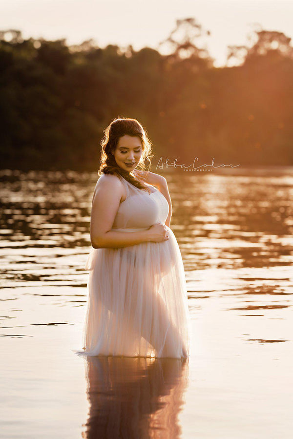 Pregnant mother in the Kaitlyn Gown by Sew Trendy Accessories in Champagne in a lake.