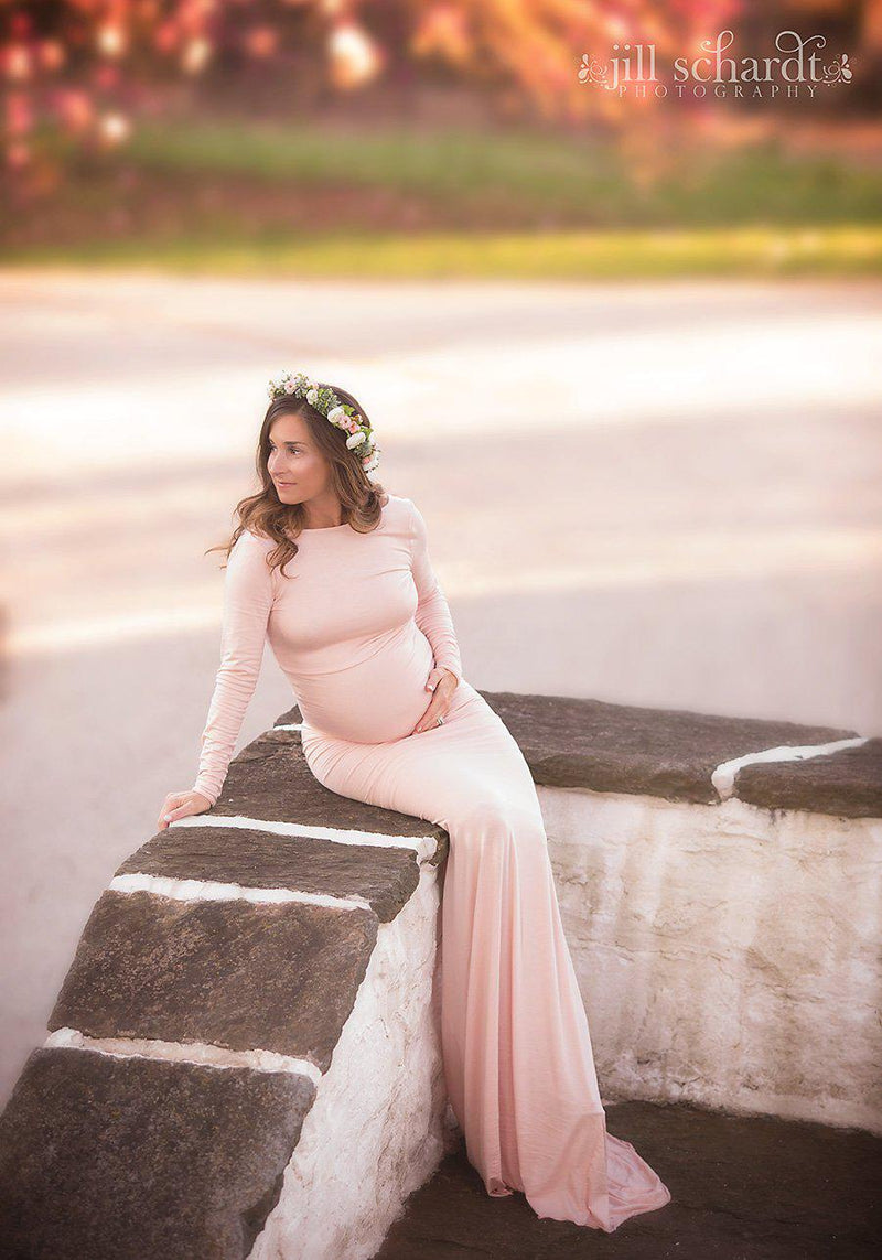 Pregnant mother in the Krysten Gown by Sew Trendy Accessories in Blush with a flower crown sitting on a wall.