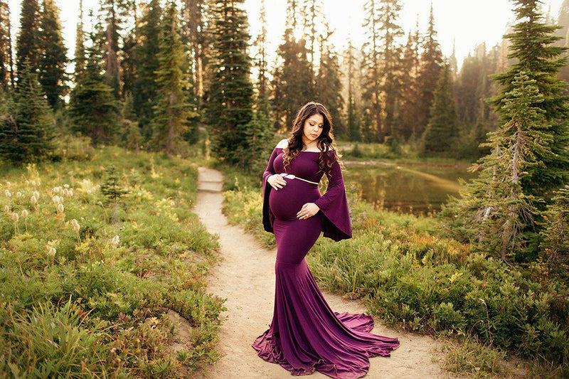 Pregnant mother in the Meredith Gown in Plum by Sew Trendy Accessories on a path with a pond.