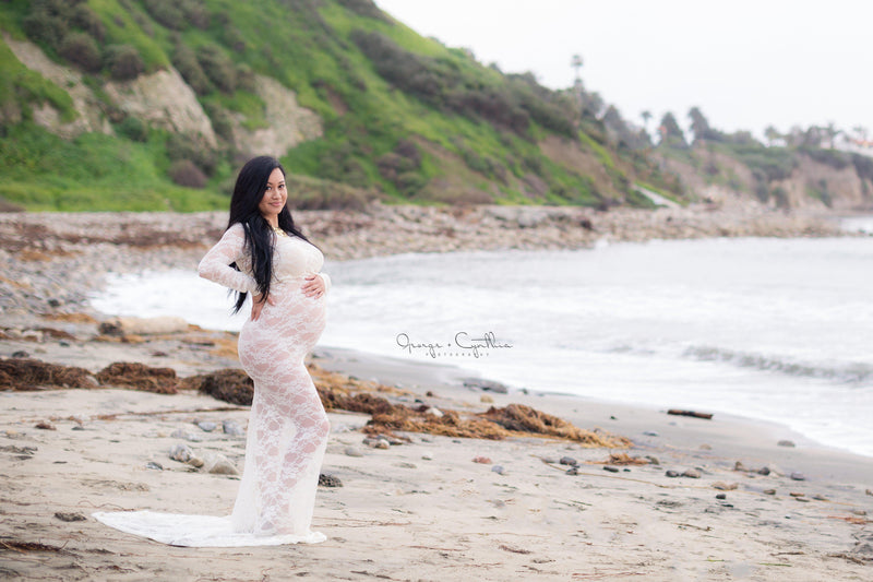 Pregnant woman in the Phoebe Gown in White by Sew Trendy Accessories standing on the beach.