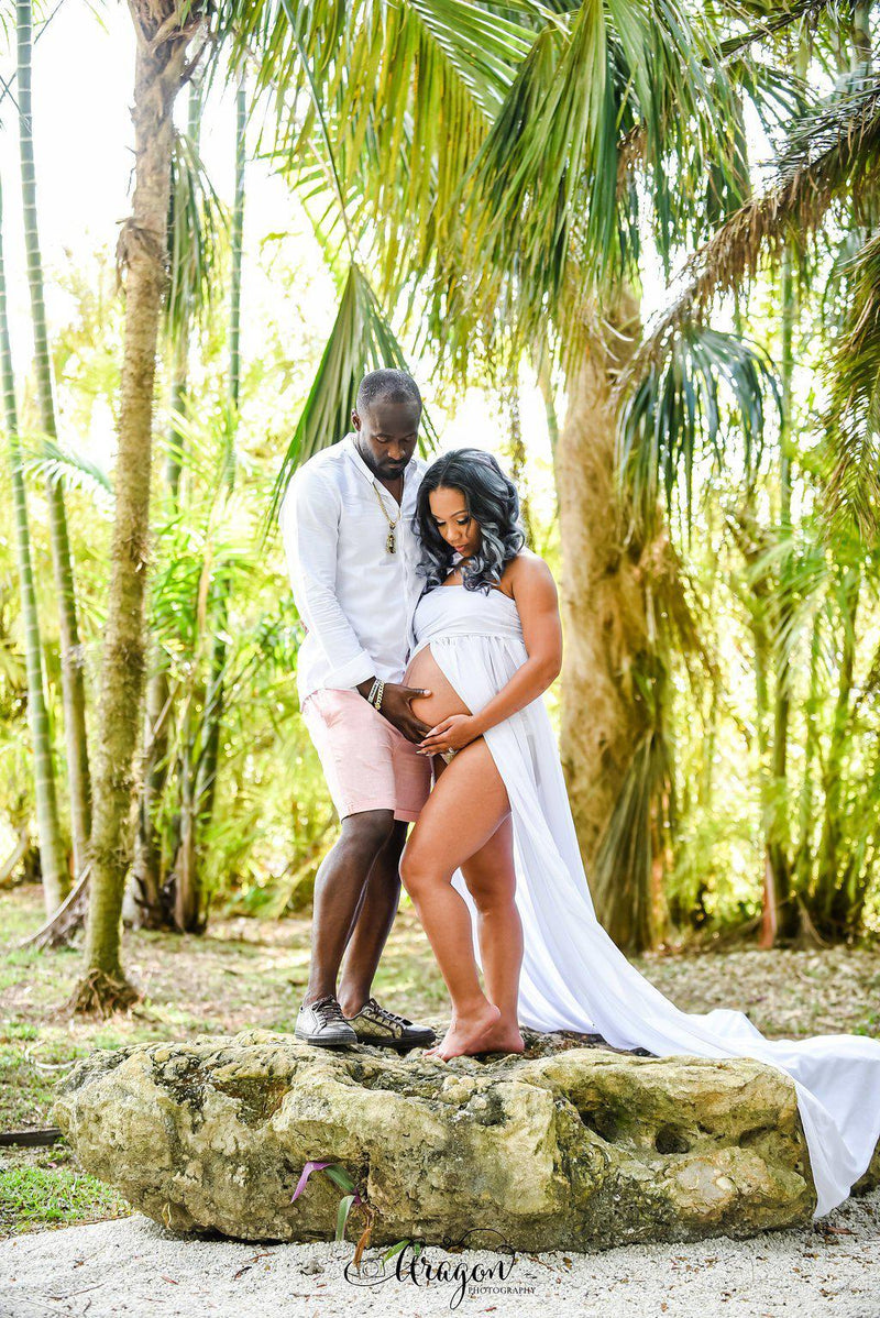 Pregnant Woman in the Rachel Gown in Ivory by Sew Trendy Accessories standing with a man in front of palm trees.