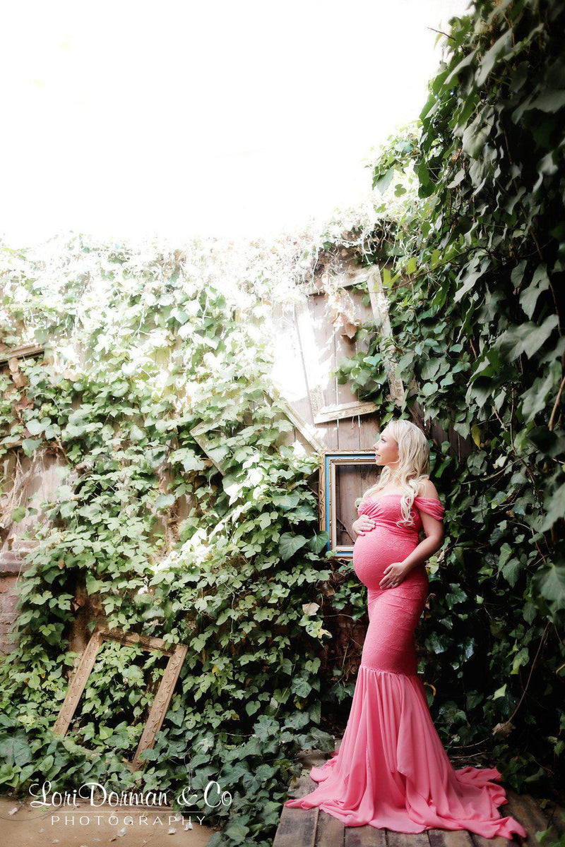 Expecting mother wearing the Samantha in coral by Sew Trendy standing near ivy covered wall
