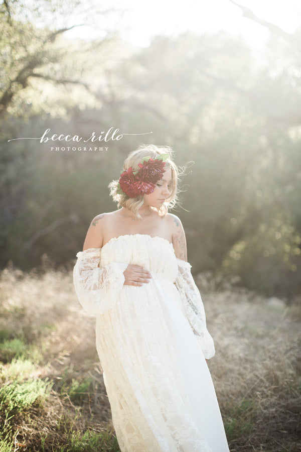 Expecting mother wearing the Valerie gown in ivory by Sew Trendy standing in field at golden hour