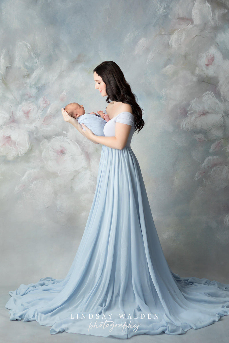 New mother holding her newborn and wearing the Faythe gown in blue rain by Sew Trendy standing in studio with floral backdrop