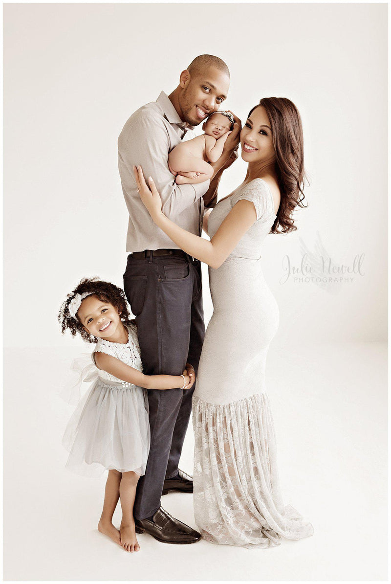 Beautiful woman wearing the bella gown in grey by Sew Trendy standing in studio with her husband and daughter.