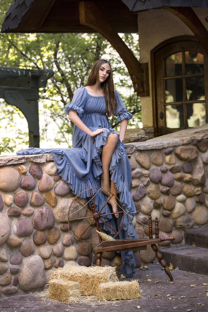 Model in the Paulina Gown in Blue Steel by Sew Trendy Accessories sitting on a rock wall in front of hay.