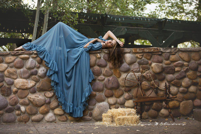 Model in the Paulina Gown in Blue Steel by Sew Trendy Accessories standing laying on a brick wall.