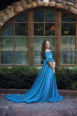 Model in the Paulina Gown in Blue Steel by Sew Trendy Accessories standing in front of windows.