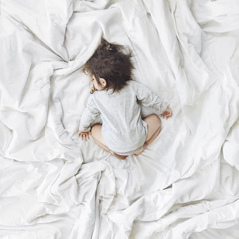 baby sleeping on white bed sheets