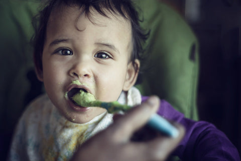 baby eating food from a plastic spoon