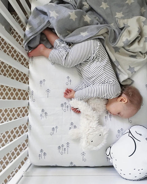 Baby holding a yeti teddy and sleeping in a cot