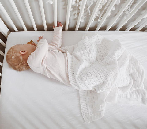 Baby sleeping on side in crib with white surroundings