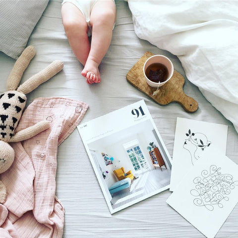 Baby on bed with coffee and magazines flatlay
