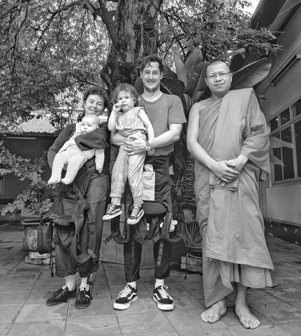 Dad and mum with their two children next to a monk on holiday in Asia