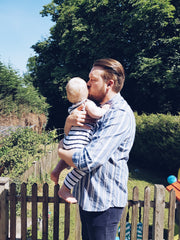 dad and child in garden kissing