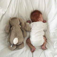 baby with rabbit teddy on bed