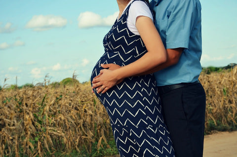 pregnant couple holding belly